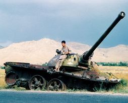 A boy on the wreckage of a tank in Afghanistan